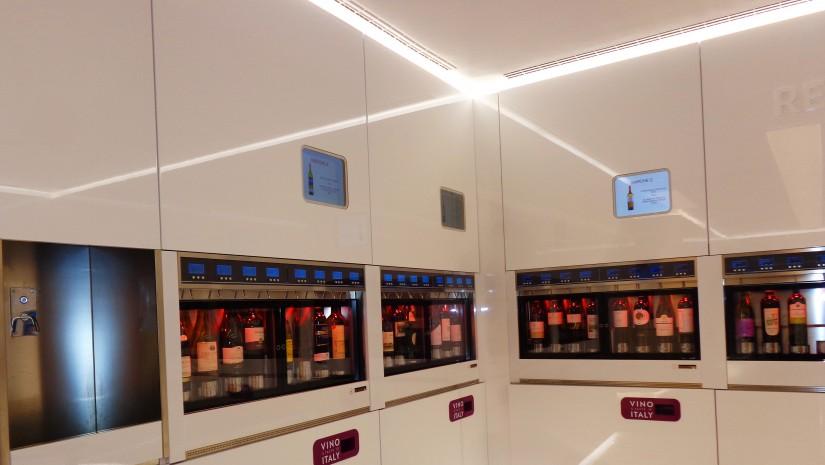 """Nowoczesna kuchnia z domu Jetsonów? Nic z tych rzeczy! To innowacyjna koncepcja włoskiego Pawilonu Wina (""""Vino A Taste Of Italy"""") – wbudowane w ścianę skrytki kryją butelki wina, zapewniając mu idealną temperaturę. Przy wejściu każdy odwiedzający otrzymuje kartę, którą można naładować na dowolną ilość euro oraz kieliszek. Następnie przykładamy kartę do gablotki z butelką wina, które nas interesuje, naciskamy przycisk i podstawiamy kieliszek pod kranik, który widać w lewej części zdjęcia i… Voilà! Już po chwili możemy raczyć się znakomitym trunkiem."""